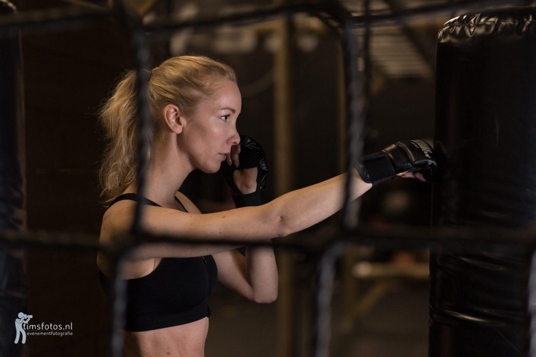 Met Bo in de sportschool. Model Bo oefent boxen op een boxpaal, net.